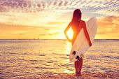 picture of sunny beach  - Surfer girl surfing looking at ocean beach sunset - JPG