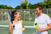 Постер, плакат: Tennis sport couple relaxing after playing game of tennis outside in summer Happy smiling friends