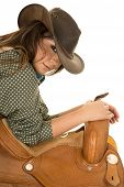picture of cowgirls  - a cowgirl leaning on a saddle with a sensual expression - JPG