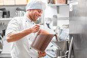 stock photo of confectioners  - Handsome confectioner in chef uniform producing ice cream with ice cream machine - JPG