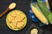 pic of corn  - Overhead shot of homemade baked corn chips on plate with cornmeal corn cobs and corn kernels in mortar photographed on dark wood with natural light - JPG