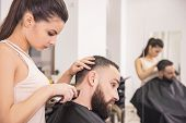 stock photo of clippers  - Hairdresser cuts hair with hair clipper on back of the head in hairdressing salon