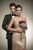 pic of she-male  - Elegant man holding his wife from the back while she is holding a bunch of red roses in her hands - JPG
