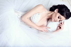 picture of studio  - fashion studio photo of beautiful elegant bride with dark hair in luxurious wedding dress