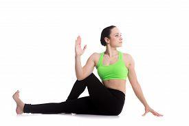 stock photo of ashtanga vinyasa yoga  - Beautiful athletic girl practicing seated spinal twist Half lord of the fishes pose Ardha Matsyendrasana yoga for back and hips - JPG