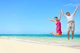 foto of jumping  - Happy couple tourists jumping on beach vacations - JPG