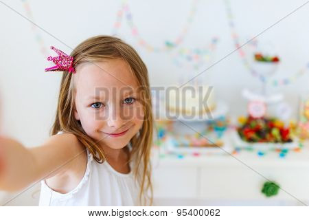 Adorable little girl with princess crown at kids birthday party taking selfie
