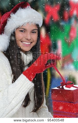 Attractive smiling teenage girl opening a Christmas Present. She is wearing a white sweater and a Santa hat. Vertical format with out of focus background and snow effect.
