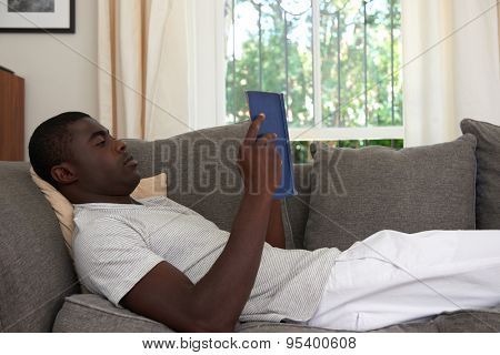 african black man relaxing on sofa couch reading literature novel story book at home living room lounge