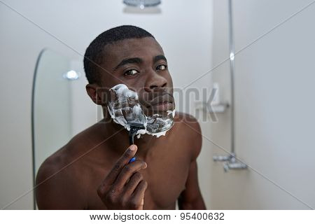 portrait of shirtless african black man shaving beard stubble face with razor in mirror reflection for morning clean shaven look in home bathroom