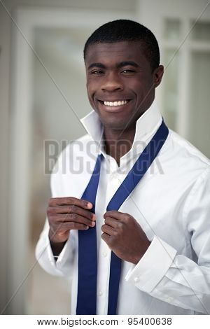 handsome professional african black man getting ready morning routine shirt and tie at home for work