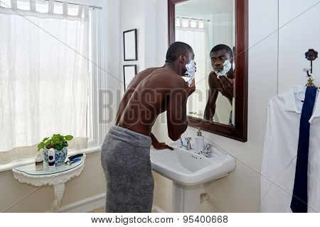 shirtless african black man applying shaving cream to face in mirror reflection for morning clean shaven look in home bathroom