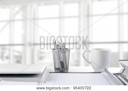 Closeup of a business desk in front of a large moder office window. The window is out of focus and high key. All items are white or silver.