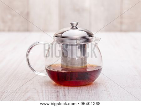 Teapot with blooming tea on wooden planks.