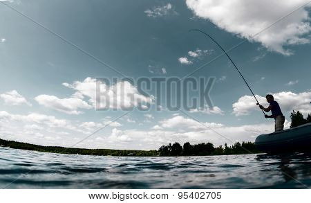 Silhouette of the young man fishing on the fresh water pond