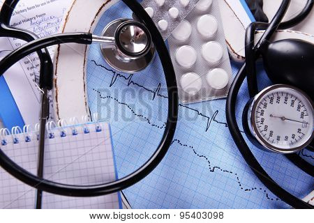 Cardiogram with stethoscope and pills on table, closeup