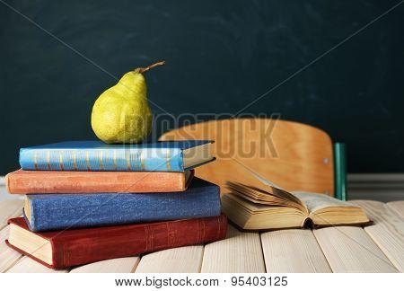 Stack of books on desk, on blackboard background