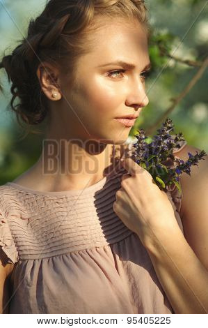 Beautiful girl with makeup and hairdo with tress holding violet flowers in her hand, summertime.