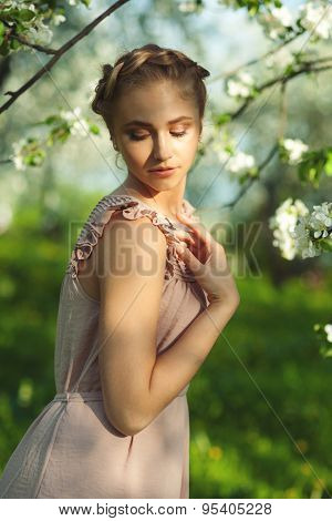 Beautiful girl with makeup and hairdo in spring garden. Girl with flowers, spring time.