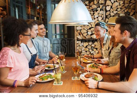 people, leisure, friendship and communication concept - group of happy smiling friends eating, drinking and talking at bar or pub