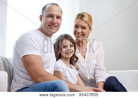 family, children and people concept - happy parents with little daughter at home