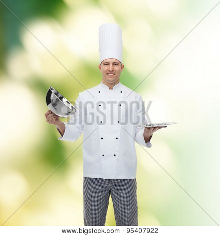 cooking, profession and people concept - happy male chef cook opening cloche cover over green background
