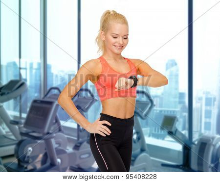 fitness, sport, technology, people and exercising concept - smiling woman looking at heart rate watch on hand over gym machines background