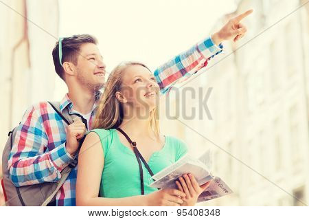 travel, vacation and friendship concept - smiling couple with city guide and backpack in city
