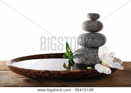 Spa stones with alstroemeria and bamboo in wooden tray with water isolated on white