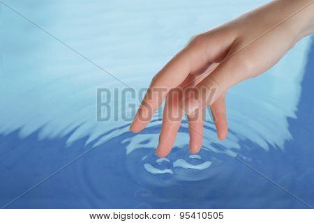 Finger touches water close up