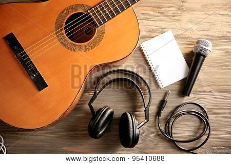 Music recording scene with classical guitar and headphones on wooden table, closeup