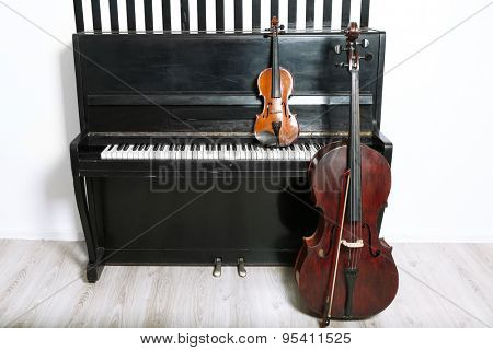 Piano, cello and violin on white wall background