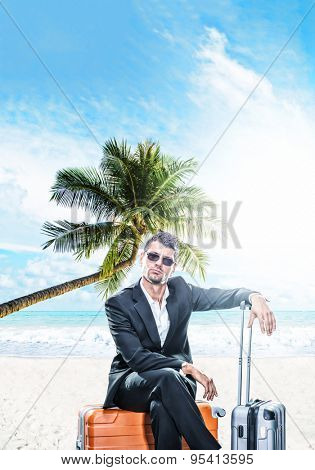 Man in suit sitting on a suitcase at the tropical beach