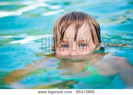 Little blond girl with blue eyes just emerged from the water in a pool. The pool is located in the courtyard of a house and the blue summer sky reflecting in water.