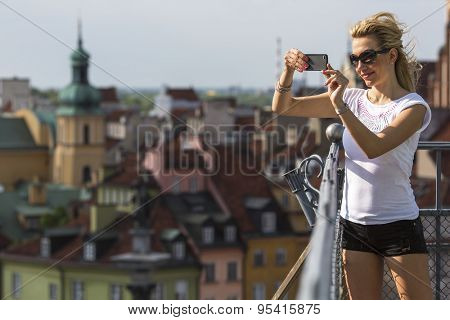 Beautiful young blondie woman taking pictures on your smartphone with a lookout tower historical center of Warsaw. Travel in Eastern Europe, leisure and tourism.