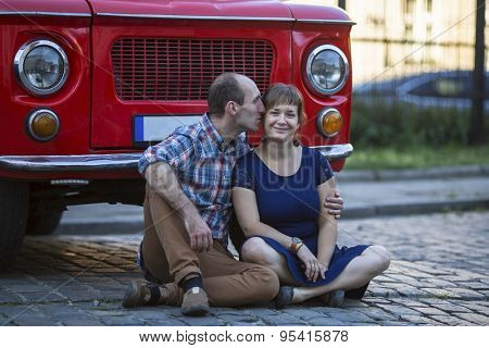 Happy young family. Couple in love sitting on the pavement near a vintage seventies style car.