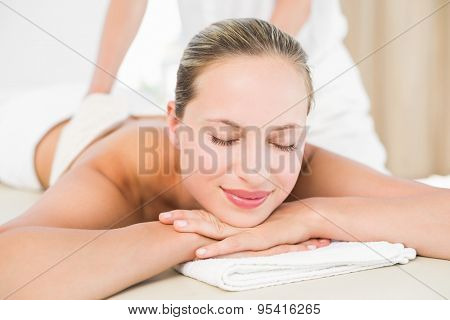 Peaceful blonde enjoying an exfoliating back massage in the health spa