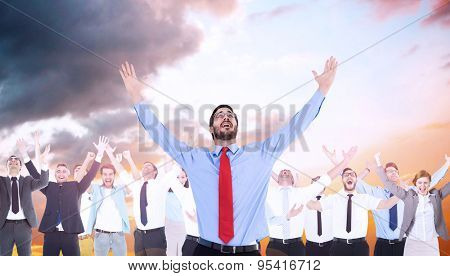 Happy cheering businessman raising his arms against orange and blue sky with clouds