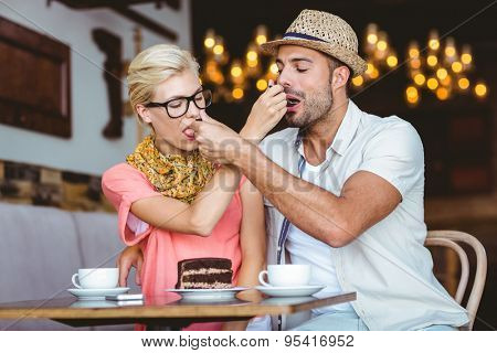 Cute couple on a date giving each other food at the cafe