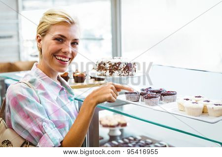 Portrait of a pretty woman pointing at cup cakes