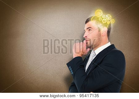 Frowning businessman thinking against grey