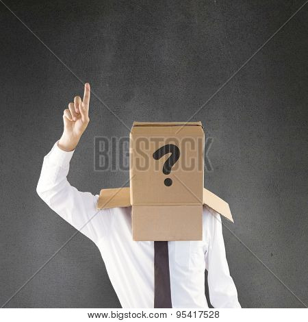 Anonymous businessman with hand pointing up against grey room