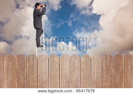Businessman standing on ladder using binoculars against fence under blue sky
