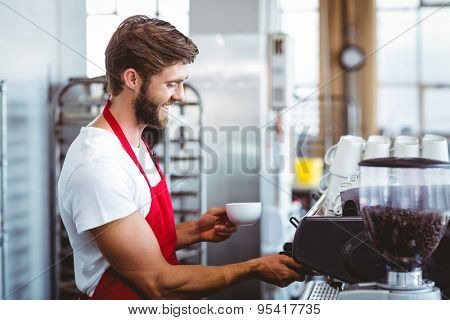 Handsome barista using the coffee machine at the cafe