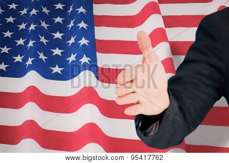 Businessman extending arm for handshake against rippled us flag
