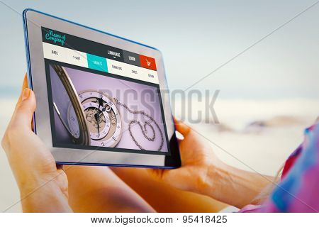 Woman sitting on beach in deck chair using tablet pc against website design