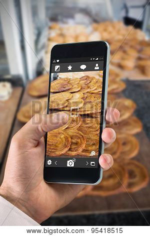 hand holding smartphone against french pastry in a palm shape on counter