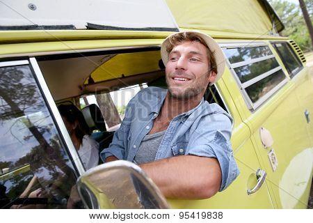 Trendy guy riding a vintage camper van