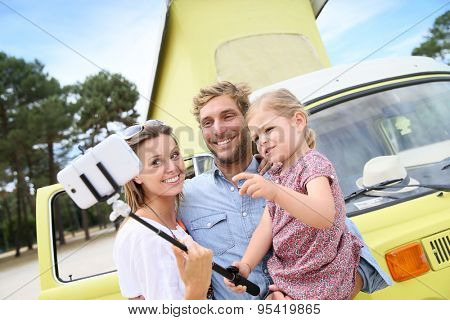 Family standing in front of camper van taking selfie picture