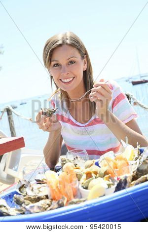 Cheerful woman tasting fresh oysters by the beach